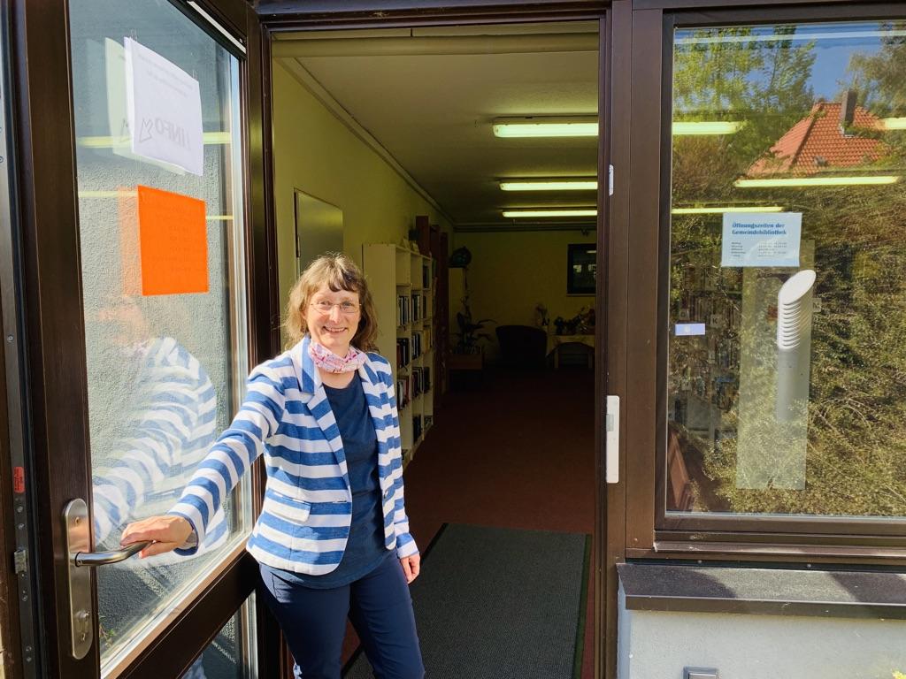 Frau Herrmann öffnet die Tür zur Gemeindebibliothek Seebach