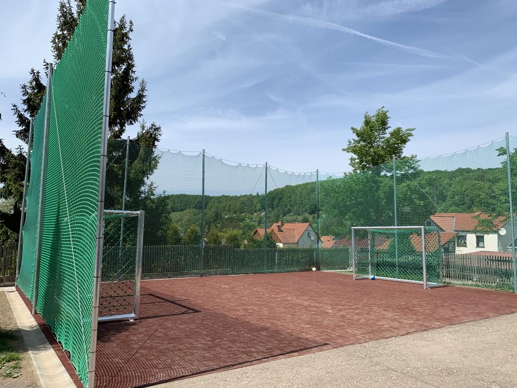 Rote Pflastersteine mit zwei Fußballtoren umgeben von einem grünen Schutznetz.