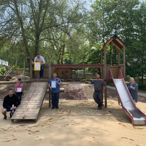 Großes Spielgerät mit Rutsche im Sandkasten. Darauf mit Abstand verteilt die Akteure rund um die Neugestaltung des Schulhofes.