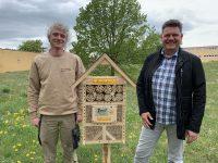 Christian Zarate und Gerrit Häcker stehen neben einem Insektenhotel