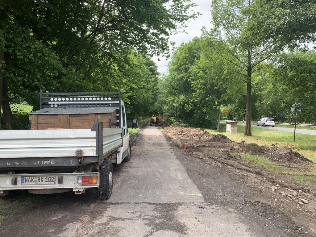 Ein Baufahrzeug steht am Rande des Radweges. Im Hintergrund arbeitet ein Bagger.