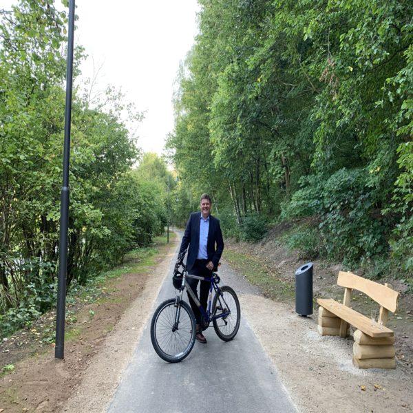 Gerrit Häcker steht mit einem Fahrrad auf dem sanierten Radweg zwischen Seebach und Thal neben einer neuen Bank und neuen Laterne.
