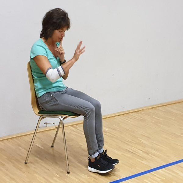 Chorleiterin Katrin Ortmann sitzt auf einem Stuhl und hört dem Chor konzentriert zu.