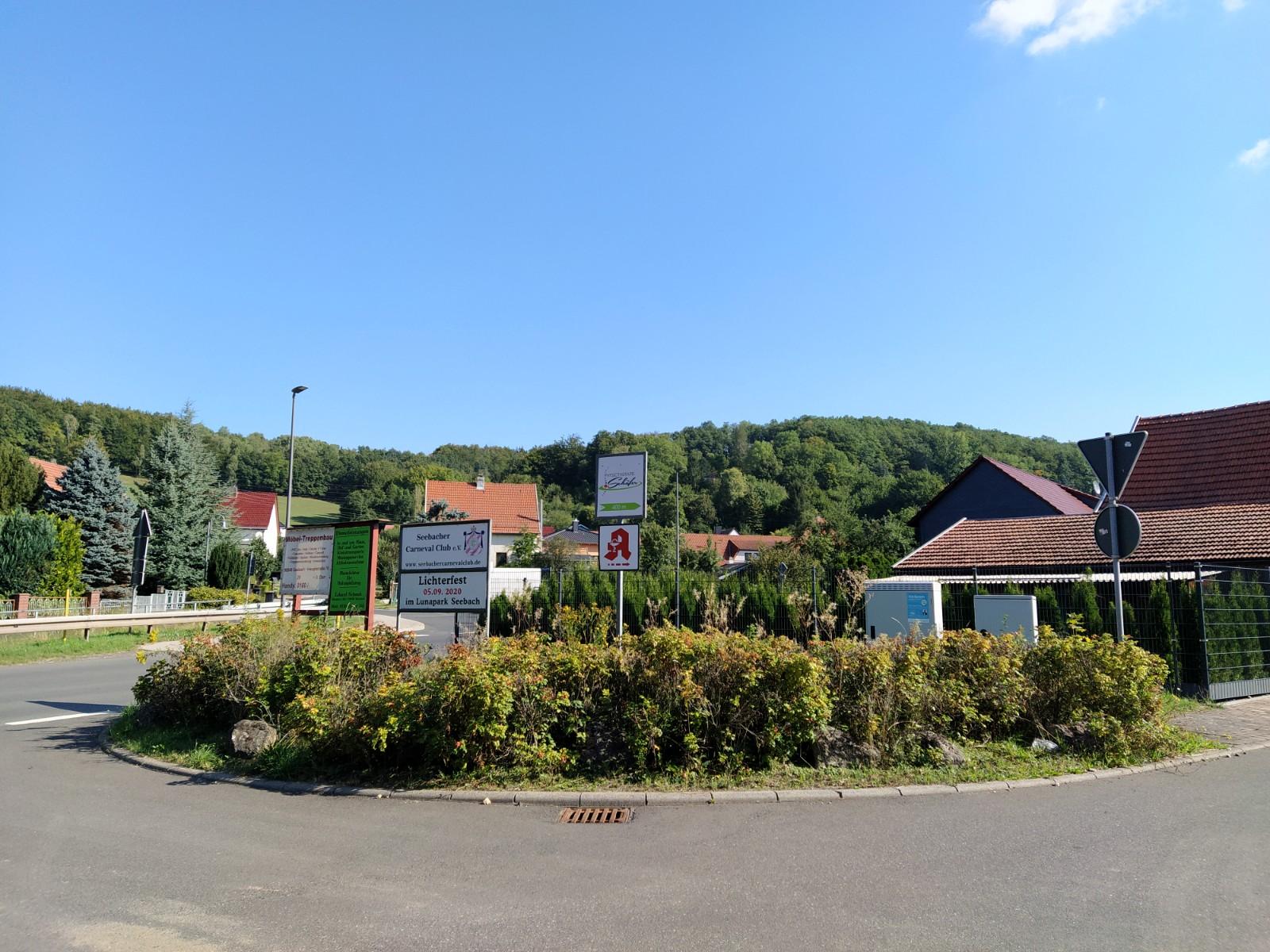 Ortseingang der Gemeinde Seebach, Hauptstraße mit Blick auf eine Reihe Sträucher am Straßenrand.