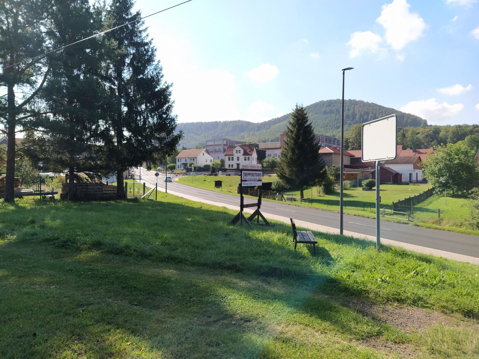 Blick auf die Neue Straße in Seebach vom Petersberg aus. Eine Wiese mit Bank am Straßenrand.