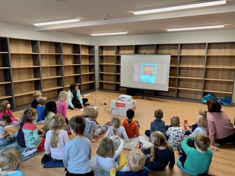 Vorschulkinder der Kindertagesstätte Wartbergzwerge sitzen im Halbkreis der Bibliothek vor einer Leinwand und hören der Bibliothekarin Claudia Herrmann zu.