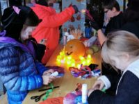 Vier Kinder basteln draußen an einem Tisch Monster und Fledermäuse