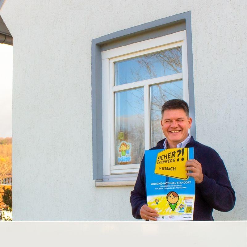 Bürgermeister Gerrit Häcker steht mit einem Notinsel Plakat in der Hand vor dem Gebäude der Gemeinde Seebach.