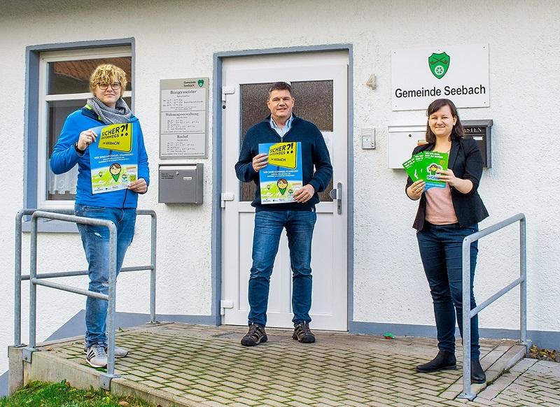 Franziska Löhr, Bürgermeister Gerrit Häcker und Mitarbeiterin Julia Patzenhauer stehen mit den Notinsel-Plakaten und Flyern vor der Tür der Gemeinde Seebach.