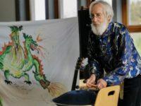 Johannes Wunderlich spielt die Pan Drum während er sein Märchen erzählt. Im Hintergrund sieht man ein Plakat mit einem Drachen.