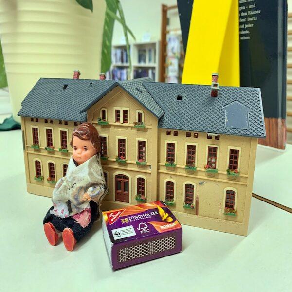 Eine kleine Puppe sitzt vor einem Spielzeughaus, daneben liegt eine Streichholzschachtel