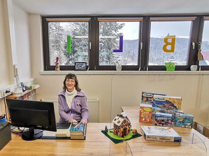 Bibliothekarin Claudia Herrmann sitzt an der neuen Rezeption der Gemeindebibliothek Seebach und präsentiert Bücher und Spiele zum Ausleihen.