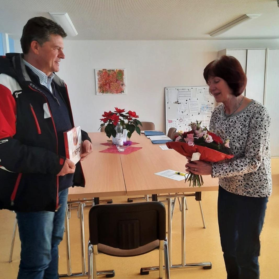 Bürgermeister Gerrit Häcker überreicht Inge Schröder Blumen und ein Geschenk zum 45-jährigen Dienstjubiläum